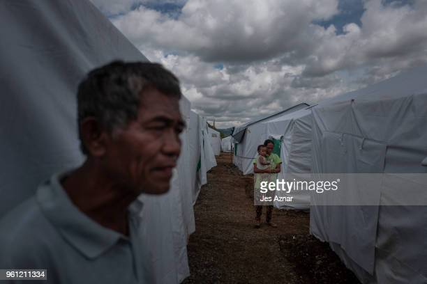 Displaced Marawi residents walk in between tents inside the Sarimanok tent city on May 14 2018 in Marawi Philippines With their homes destroyed and...
