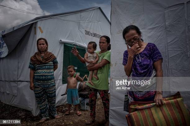 Displaced Marawi residents walk in between tents with their belongings inside the Sarimanok tent city on May 14 2018 in Marawi Philippines With their...