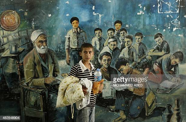 A displaced Palestinian boy from Beit Hanun in the northern Gaza Strip stands on July 23 2014 in front of a mural painting at a UN school in thre...