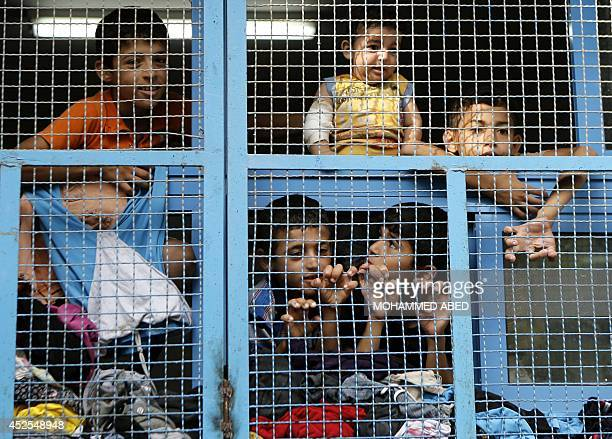 Displaced Palestinian children from Beit Hanun in the northern Gaza Strip stand behind the window of a classroom on July 23 2014 at a UN school in...