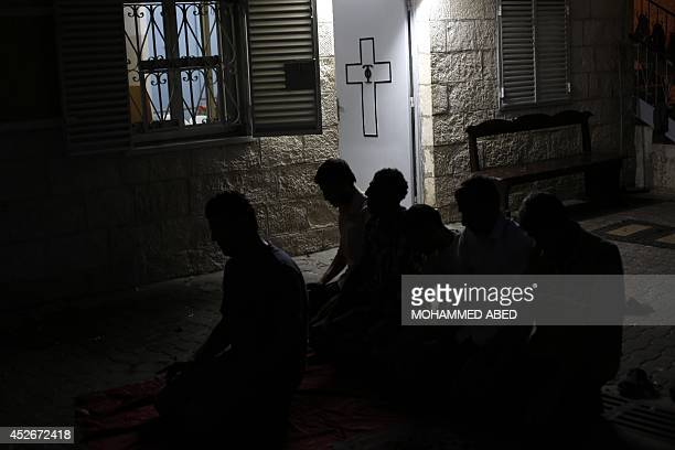 Displaced Palestinian pray inside a Greek Orthodox church where many Palestinians are taking shelter in Gaza City on July 25 2014 US Secretary of...