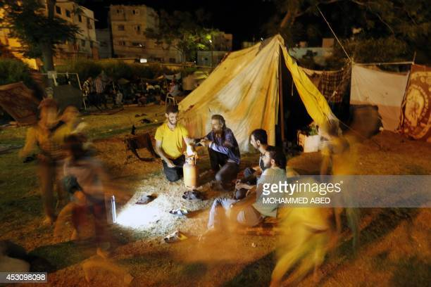 Displaced Palestinians sit outside a makeshift tent on August 2 2014 at alShifa hospital in Gaza City where families found refuge after fleeing their...