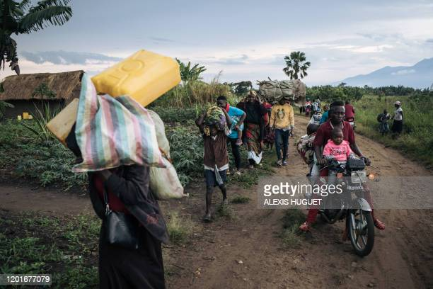 Displaced people carrying their belongings flee the scene of an attack allegedly perpetrated by the rebel group Allied Democratic Forces in the...