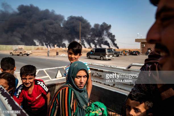Displaced people fleeing from the countryside of the Syrian Kurdish town of Ras alAin along the border with Turkey ride in the back of a pickup truck...