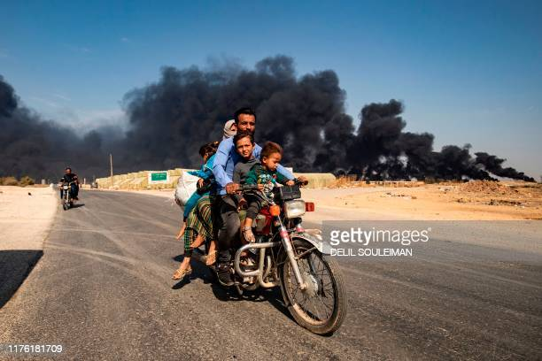 Displaced people fleeing from the countryside of the Syrian Kurdish town of Ras alAin along the border with Turkey ride a motorcycle together along a...