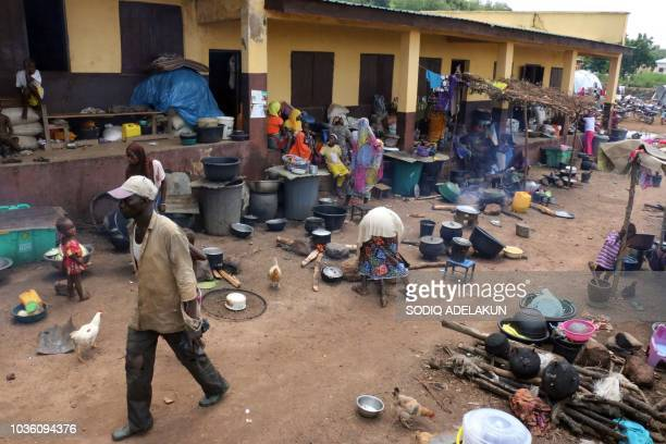 Displaced people gather at the cooking facility at an Internally displaced people camp in Lokoja, Kogi State, on September 19, 2018. - Nigeria has...