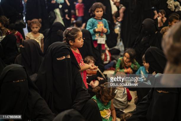 Displaced people gather before boarding a bus waiting outside the AlHol camp in northeastern Syria's AlHasakeh governorate on June 3 as Kurdish...