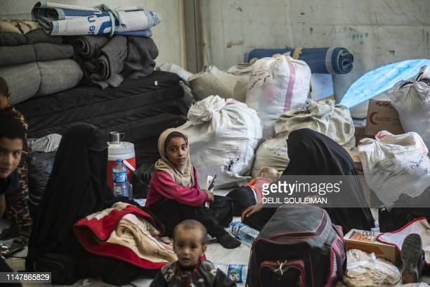 Displaced people gathers before boarding a bus waiting outside the AlHol camp in northeastern Syria's AlHasakeh governorate on June 3 as Kurdish...