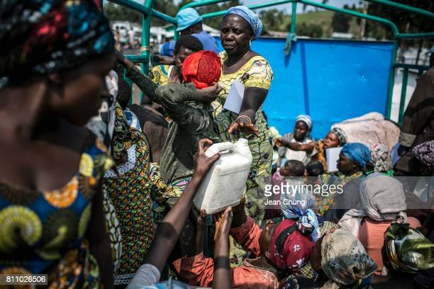 Displaced people in Mugunga I IDP camp hand over a water container on a truck to return to Kibati and Mujoga as a part of the Voluntary Return...