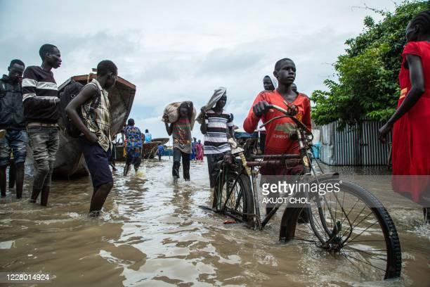 Displaced people walk with their belongings in a flooded area after the Nile river overflowed after continuous heavy rain which caused thousands of...