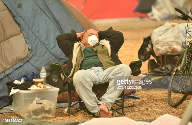 A displaced person sleeps at an evacuee encampment in a Walmart parking lot in Chico California on November 15 2018 The toll in the deadliest...