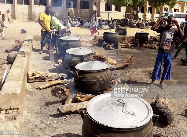 Displaced persons prepare food for lunch in an openair kitchen for people displaced by Boko Haram violence on May 19 2016 in the Dalori Internally...