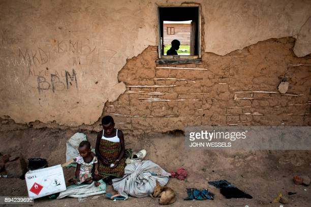 TOPSHOT Displaced pygmies sit with their belongings outside a classroom which serves as their shelter by night on December 16 2017 in Oicha Displaced...