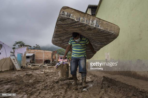 A displaced resident carries a matteress and bucket of supplies after a landslide in the San Miguel neighborhood of Mocoa Putumayo Colombia on Monday...