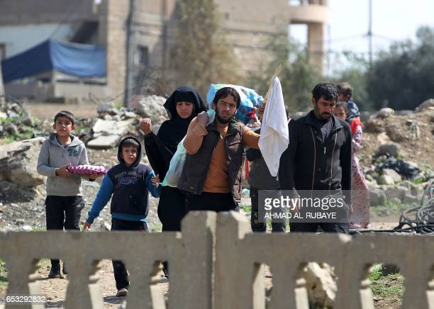 Displaced residents from Mosul's alNasser neighbourhood wave a white flag as they evacuate the area on March 14 2017 while Iraqi forces continue to...