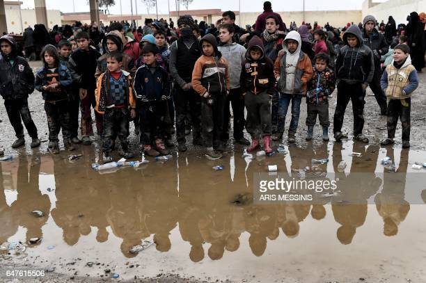 TOPSHOT Displaced residents of Mosul gather at a gasoline station used as a gathering point after fleeing Mosul on March 3 during an offensive by...