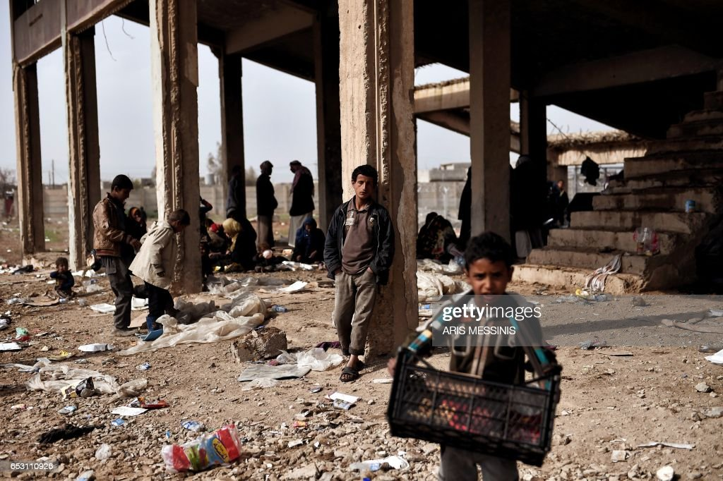 TOPSHOT - Displaced residents of the Iraqi city of Mosul gather at an empty building where they are taking shelter as they wait for space at the Hamam al- Alil camp for internally displaced people ...