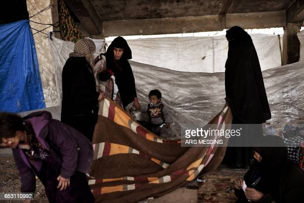 Displaced residents of the Iraqi city of Mosul gather at an empty building where they are taking shelter as they wait for space at the Hamam al Alil...