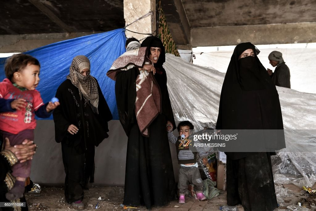 Displaced residents of the Iraqi city of Mosul gather at an empty building where they are taking shelter as they wait for space at the Hamam al- Alil camp for internally displaced people (IDP) on March 13, 2017. Fleeing the fighting in Mosul-West, where the Iraqi security forces are pursuing an offensive to drive out the jihadists from the Islamic state (IS), tens of thousands of civilians have joined IDP camps hastily built in the vicinity of the second largest city in Iraq. /