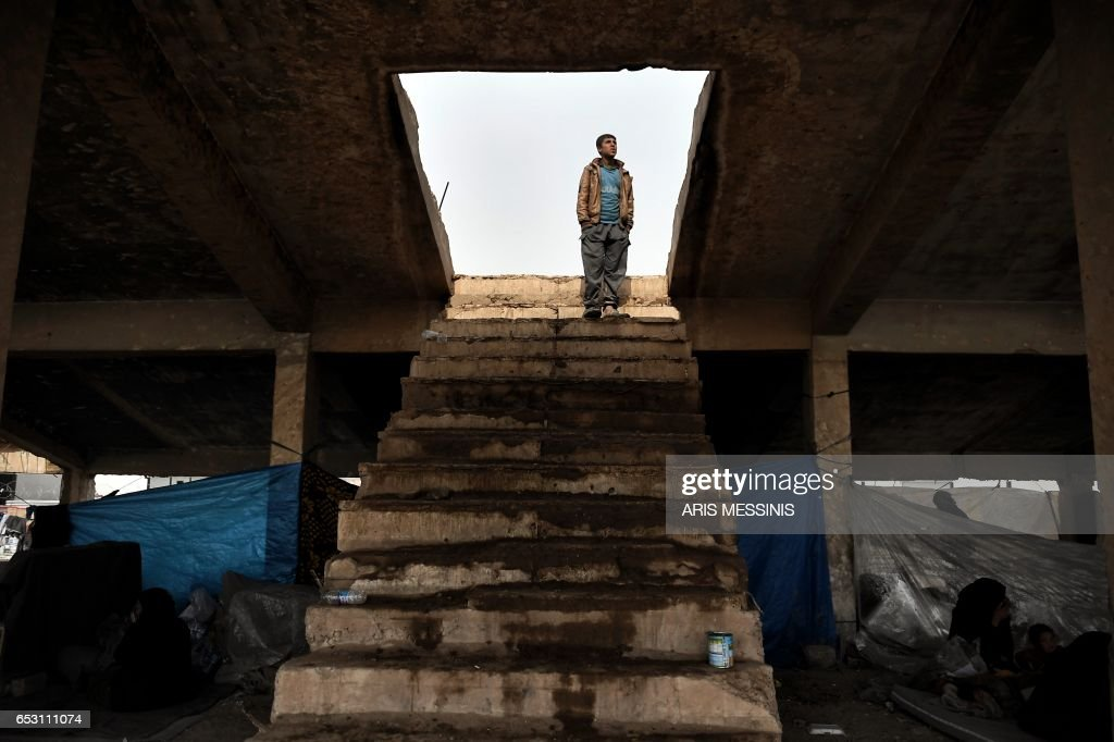TOPSHOT - Displaced residents of the Iraqi city of Mosul gather at an empty building where they are taking shelter as they wait for space at the Hamam al- Alil camp for internally displaced people (IDP) on March 13, 2017. Fleeing the fighting in Mosul-West, where the Iraqi security forces are pursuing an offensive to drive out the jihadists from the Islamic state (IS), tens of thousands of civilians have joined IDP camps hastily built in the vicinity of the second largest city in Iraq. /