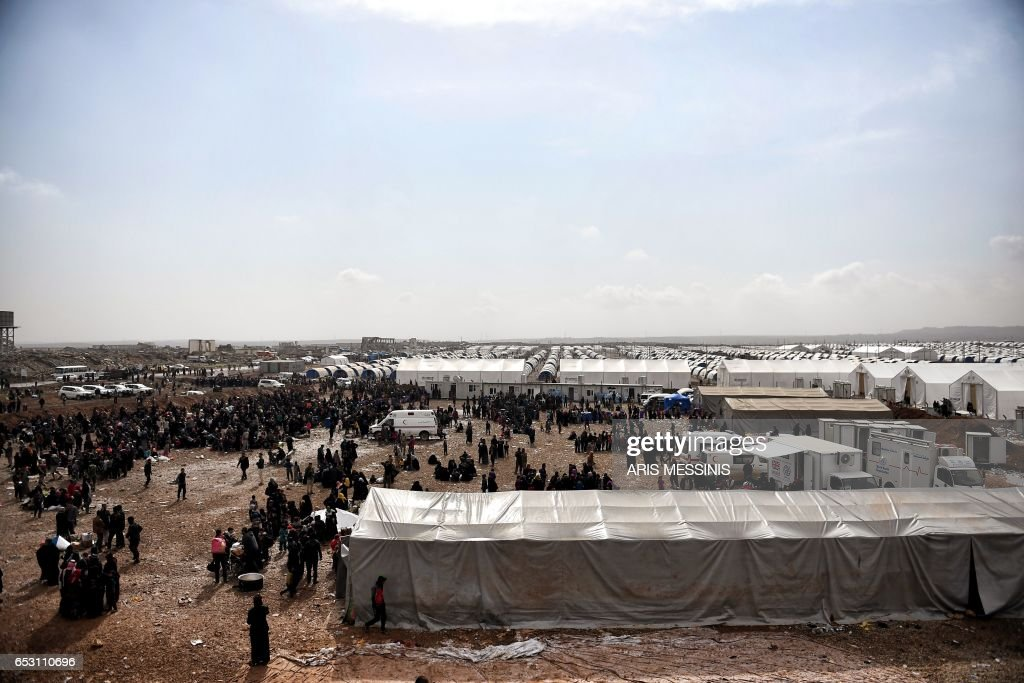 Displaced residents of the Iraqi city of Mosul gather at the Hamam al- Alil camp for internally displaced people (IDP) on March 13, 2017. Fleeing the fighting in Mosul-West, where the Iraqi security forces are pursuing an offensive to drive out the jihadists from the Islamic state (IS), tens of thousands of civilians have joined IDP camps hastily built in the vicinity of the second largest city in Iraq. /
