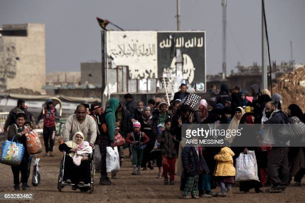 Displaced residents of western Mosul evacuate the area on March 14 2017 as Iraqi government forces continue to advance in the embattled city...