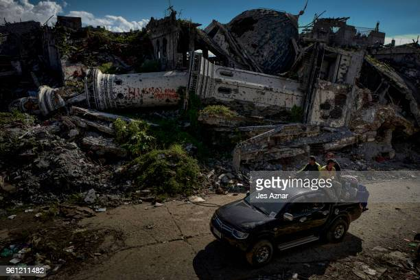 Displaced residents pass by a destroyed mosque on May 10 2018 in Marawi Philippines With their homes destroyed and their properties looted or burned...