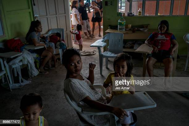 Displaced residents rest at a makeshift evacuation center in a classroom at a private school on December 26 2017 in Tubod Lanao del Norte Philippines...