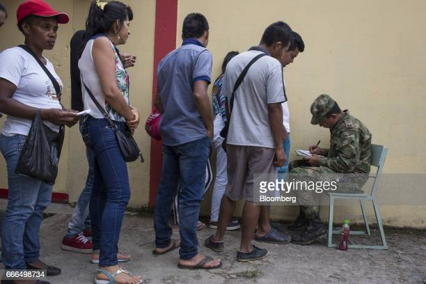 Displaced residents wait in line to provide information to a member of the military at a disaster relief center after landslides in Mocoa Putumayo...