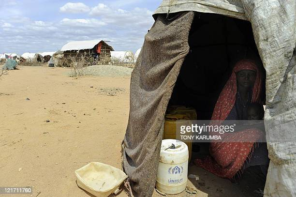A displaced Somali mother and her children take cover from the hot sun in a makeshift shelter on August 14 2011 at the Dadaab refugee complex UN...