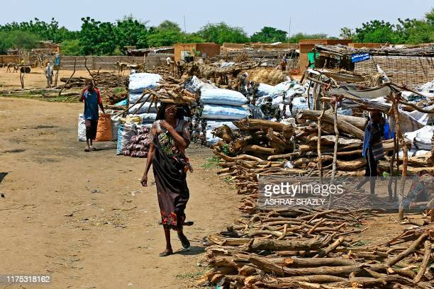 A displaced Sudanese woman carries firewood on her head at the Kalma camp for internally displaced people in Darfur's state capital Niyala on October...