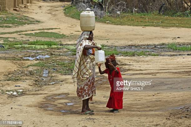 A displaced Sudanese woman carries on her head a jerry can filled with drinking water at the Kalma camp for internally displaced people in Darfur's...