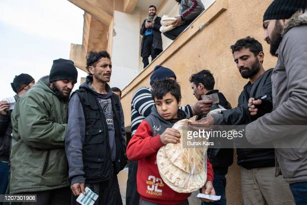 Displaced Syrian boy carries a bag of bread as people wait in a queue as an NGO delivers bread in a stadium which has been turned into a makeshift...