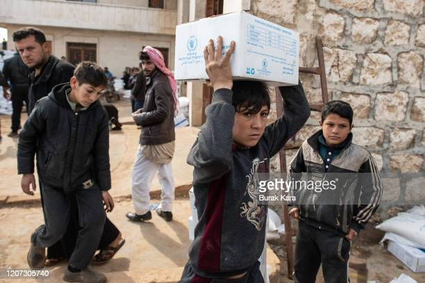 Displaced Syrian boy carries a box of humanitarian aid supplied by an NGO on February 19, 2020 in Idlib, Syria. Turkey's President Recep Tayyip...