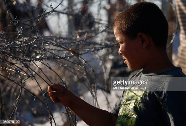 TOPSHOT A displaced Syrian boy from the Daraa province fleeing shelling by progovernment forces is seen near barbed wire in a makeshift camp to cross...