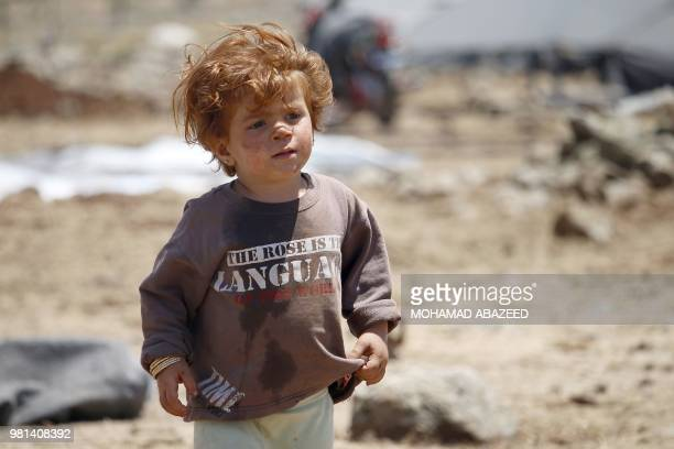 A displaced Syrian boy from the Daraa province fleeing shelling by progovernment forces waits in a makeshift camp in the province of Quneitra...