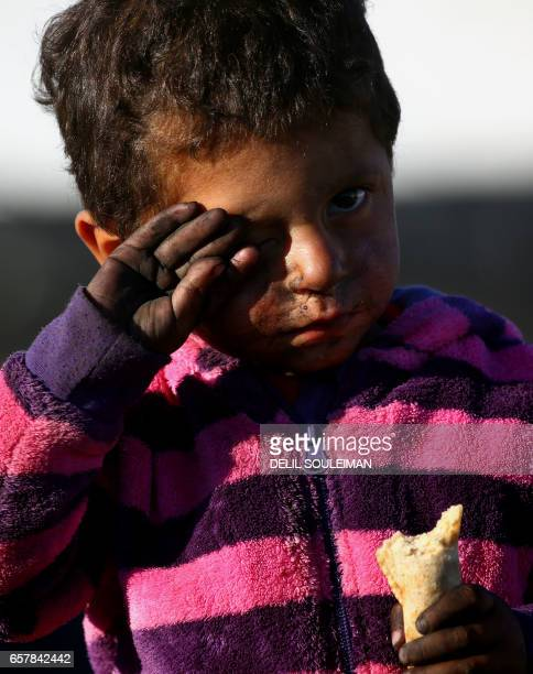 A displaced Syrian boy is seen at a temporary refugee camp in the village of Ain Issa some 50 kilometres north of Raqa sheltering people who fled the...