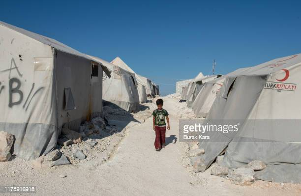 A displaced Syrian boy walks between the tents in a Turkish Red Crescent camp near the village of Atmeh which hosts nearly one million displaced...