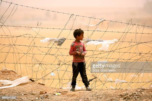 TOPSHOT A displaced Syrian boy who fled the Islamic State group stronghold of Raqa stands near a fence during a sandstorm at a temporary camp in the...