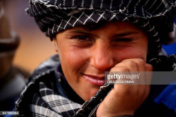 Displaced Syrian boy, who fled their hometowns due to clashes between regime forces and the Islamic State group, winks as he stands outside a tent in...