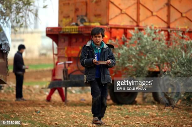 Displaced Syrian boy, who fled their hometowns due to clashes between regime forces and the Islamic State group, walks with a plate in Kharufiyah, 18...