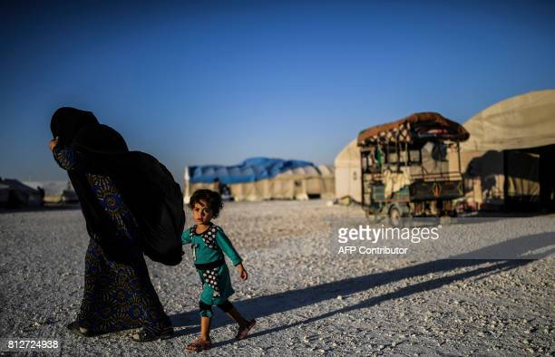 TOPSHOT A displaced Syrian child and her mother who fled the countryside surrounding the Islamic State group's stronghold of Raqa walk at a temporary...