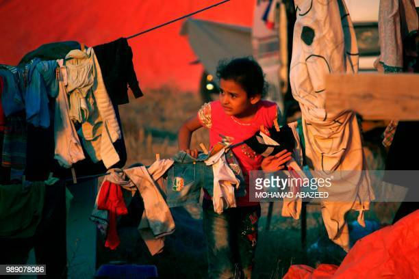 TOPSHOT A displaced Syrian child from the Daraa province fleeing shelling by progovernment forces waits in a makeshift camp to cross the Jordanian...