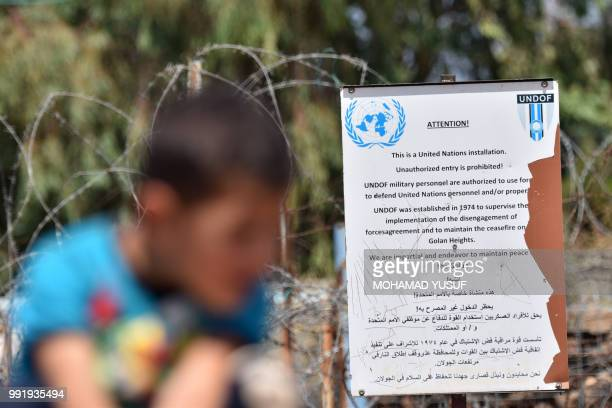 A displaced Syrian child from the province of Daraa sits near a UNDOF sign at a UN base on the border between Syria and the Israelioccupied Golan...
