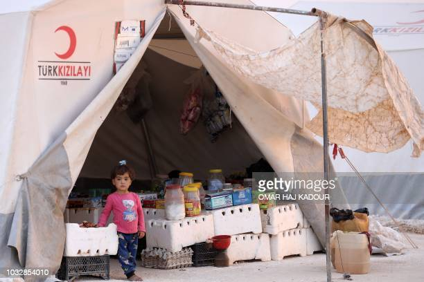 A displaced Syrian child poses for a photograph in the camp 'Hope' in the Syrian village of Kafr Lusein north of the Bab alHawa border crossing on...