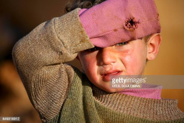 TOPSHOT A displaced Syrian child shields his eyes from the sun a makeshift camp in the village of Jab alTur on the southern outskirts of Manbij on...