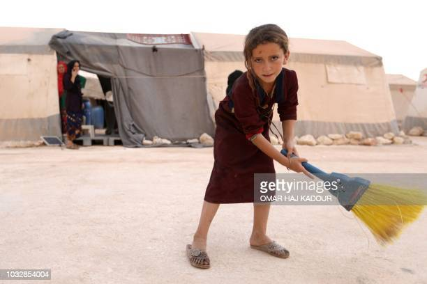 A displaced Syrian child uses a broom in the camp 'Hope' in the Syrian village of Kafr Lusein north of the Bab alHawa border crossing on September 13...