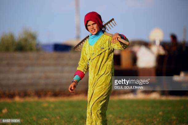 TOPSHOT A displaced Syrian child walks carrying a rake at a makeshift camp in the village of Jab alTur on the southern outskirts of Manbij on March 7...