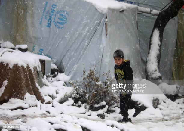 TOPSHOT A displaced Syrian child walks through a blizzard at a makeshift refugee camp near the village of Burayqah on the outskirts of southeastern...