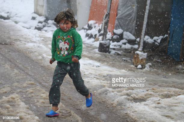 A displaced Syrian child walks through a blizzard at a makeshift refugee camp near the village of Burayqah on the outskirts of southeastern Syrian...